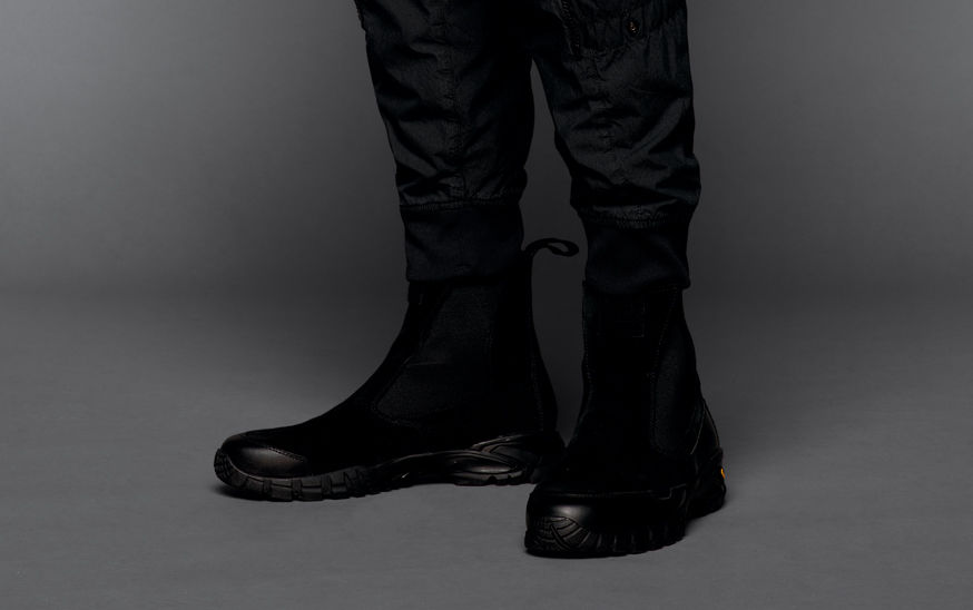 Close up shot of model wearing black boots with back tab and black pants with ribbed cuffs.