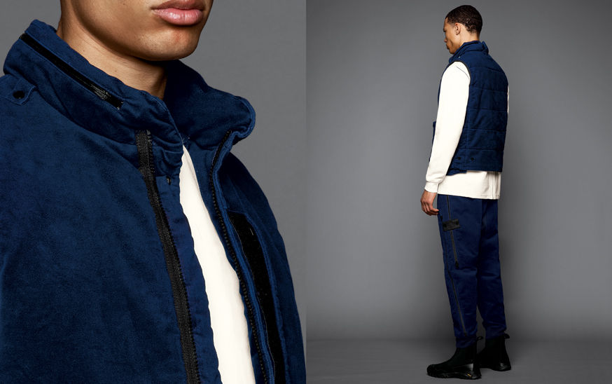 Two shots of the same model, one showing the detail of a blue jacket collar with a concealed hood, the other one a side view of the model wearing black boots, blue cargo pants, a white sweatshirt and a blue vest with standing collar.