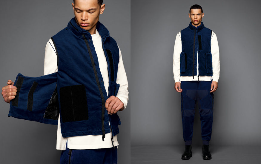 Two shots of the same model, one showing the side strap detail of a blue vest, the other one with the model wearing black boots, blue cargo pants, a white sweatshirt and a blue vest with standing collar and zipper fastening.