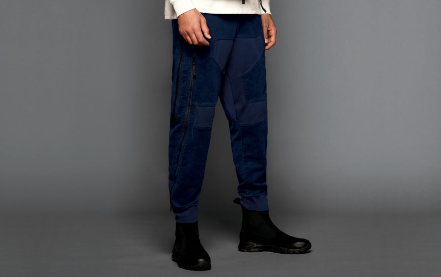 Close up of model wearing a white sweatshirt, black boots and blue pants with ribbed cuffs, side zippers and patches of different material.