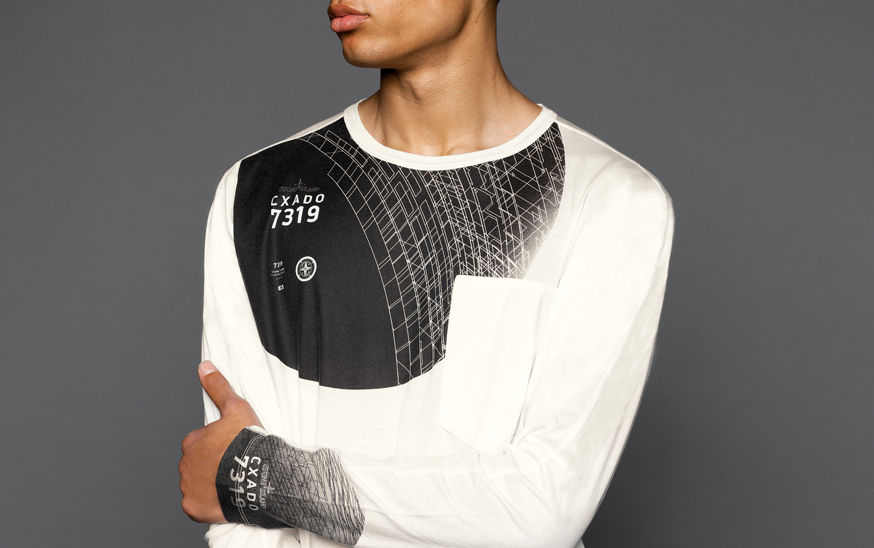 Close up of a model wearing a white t shirt with long sleeves, a breast pocket and a black and white graphic print with the brand logo and lettering that reads CXADO 7319, both across the chest and on the bottom of the sleeve.