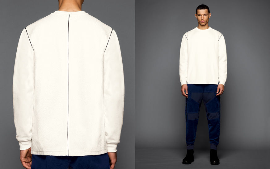 Two shots of the same model, one showing the back of a white sweatshirt with dark piping on the shoulders and down the spine, the other one with the model wearing black boots, blue pants with patches and a white crewneck sweatshirt with dark piping on the