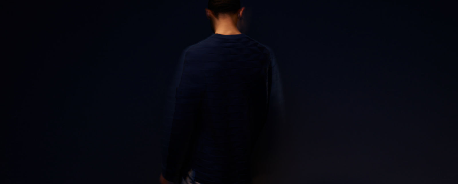 View of a model from the back wearing a dark blue crew neck sweater against a dark blue background
