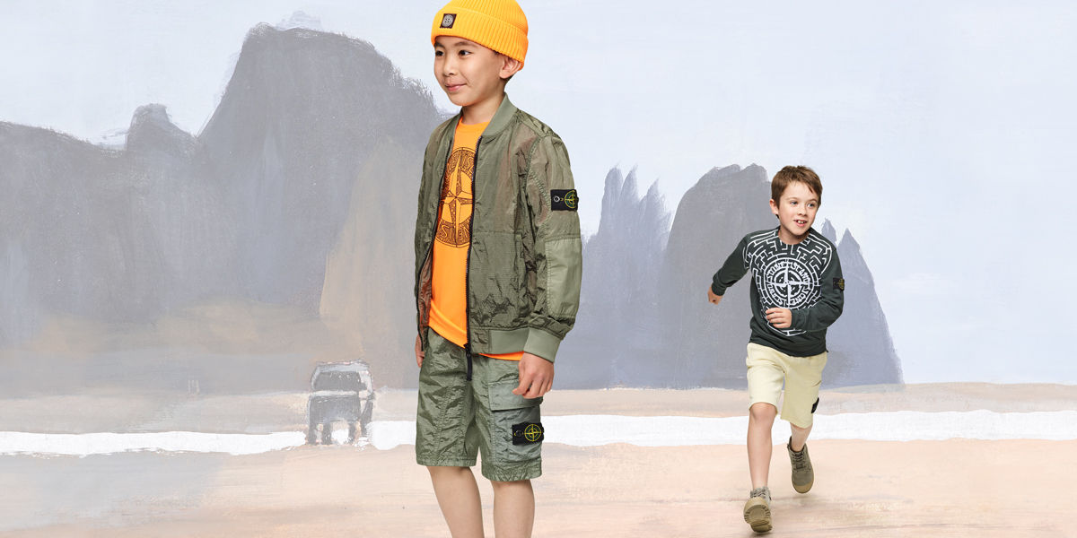 Two junior models, one wearing military green cargo shorts and light jacket, a yellow top with the Stone Island compass rose across the chest and matching beanie, the second wearing cream shorts and a dark gray sweatshirt with a graphic Stone compass rose across the chest.