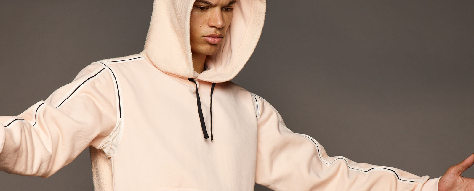 Model wearing a light peach hoodie with black and lighter peach line details along the edges of the shoulders and sleeves and black drawstrings at the hood
