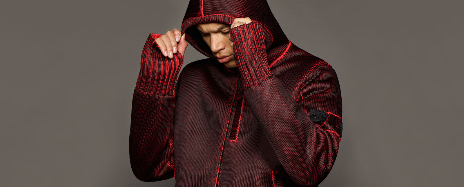 Model wearing a deep burgundy knit hoodie with bright red  line details along the seams, zipper placket, and wide ribbed cuffs