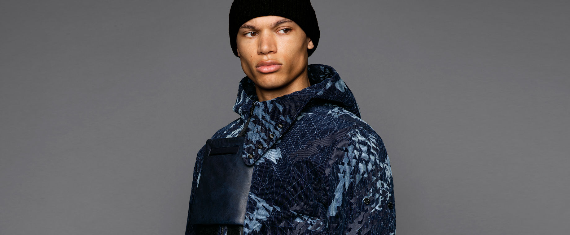Cropped portrait of a model wearing short hooded jacket in an abstract pattern of dark and light blue hues with a square leather pocket on the chest