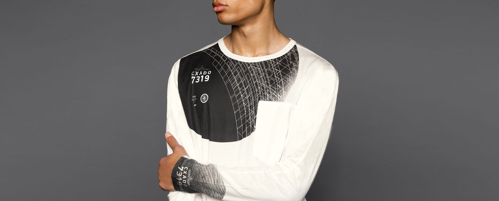 """Model wearing a  white long-sleeved T-shirt with black  inserts at the chest and sleeve cuffs featuring a pattern of white lines, logos, and \""""CXADO 7319\"""""""