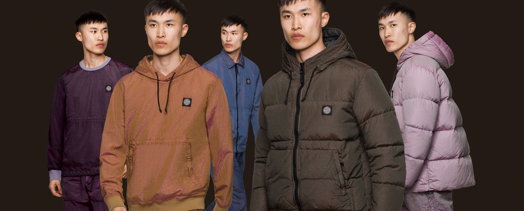 Five shots of the same model, wearing different Nylon Metal outfits with the Stone Island patch at chest: purple pants with a matching  crewneck top, a copper hooded jacket with front pouch pocket, blue pants and a matching jacket with shirt collar and zi