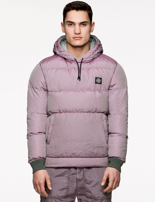 Model wearing light mauve pants and a matching padded anorak with hood and drawstring, green ribbed cuffs, pouch pocket with slanting entrances and Stone Island patch at left chest.