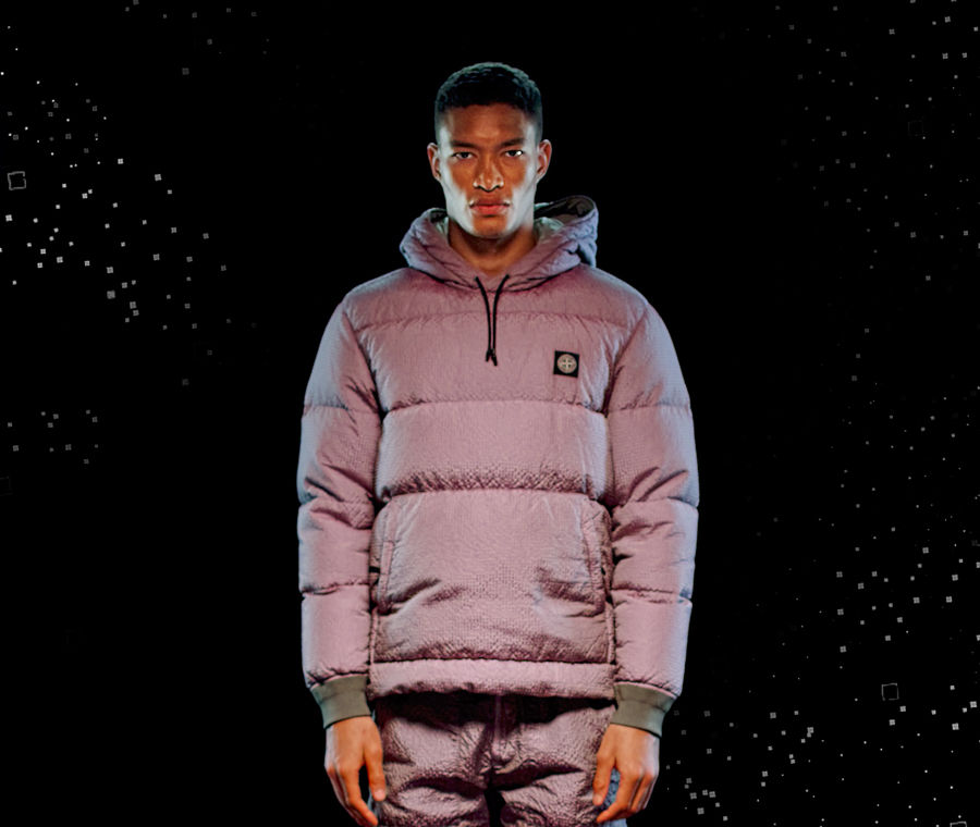 Model wearing light mauve pants and a matching padded anorak with hood and drawstring, green ribbed cuffs, pouch pocket and Stone Island patch at left chest.