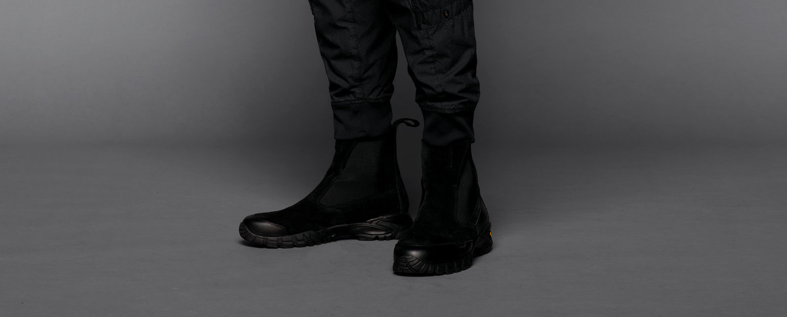 Close-up of black, Chelsea-style elasticated ankle boots with chunky, textured soles and pull tabs on a model wearing black pants