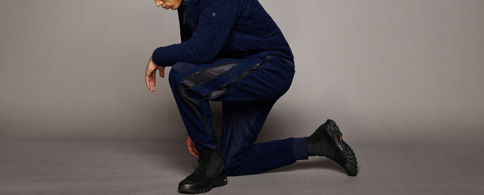 Model on one knee wearing dark blue pants with black, zippered nylon inserts along the sides of the legs and a matching dark blue jacket, with black boots