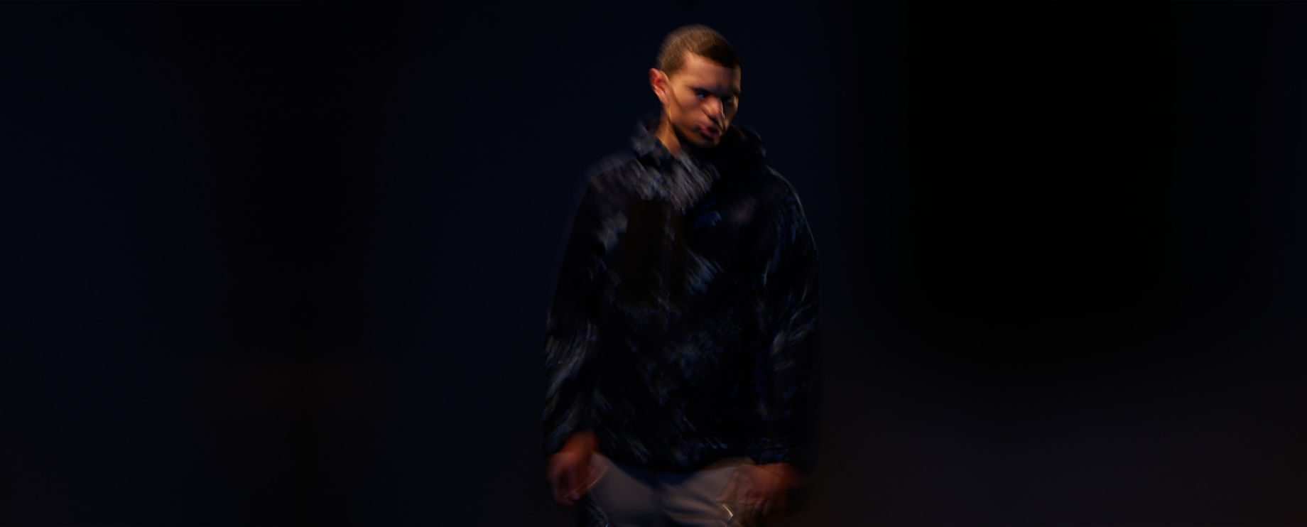 Blurred image of model wearing dark colored pants and a light pink bomber jacket with zipper fastening and slanting hand pockets.