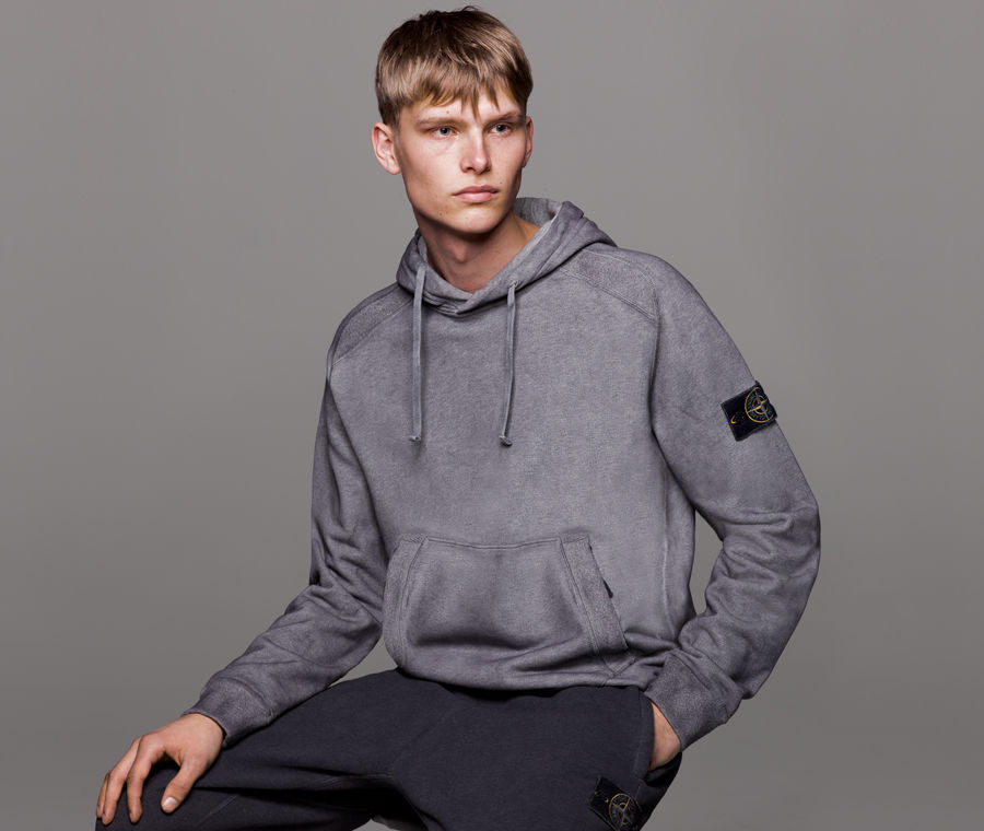 Model wearing grey hooded sweatshirt with drawstrings at the hood, kangaroo pocket, and Stone Island badge on the left sleeve.