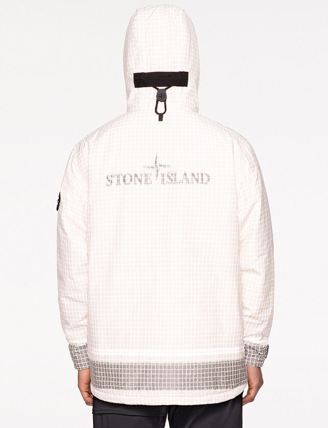 Back view of model wearing black pants and a white check print anorak with hood up, showing a black toggle, Stone Island logo at the center of the back and gray colored cuffs and bottom hem.