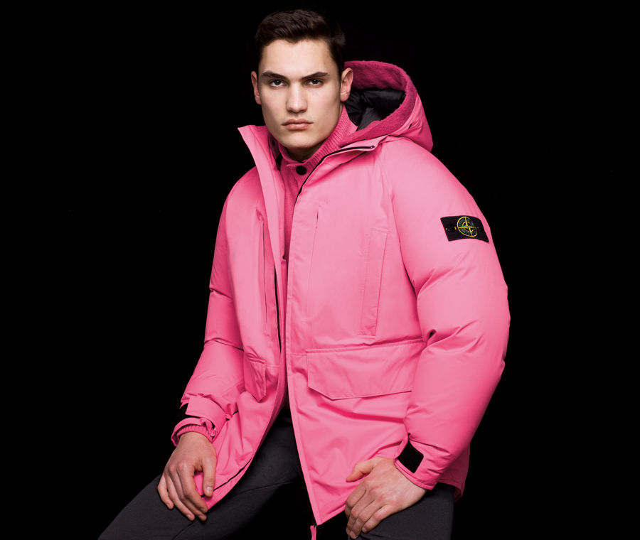 Side view of model wearing black pants and a pink hooded jacket with inner drawstring on back and the Stone Island badge on the upper left sleeve.