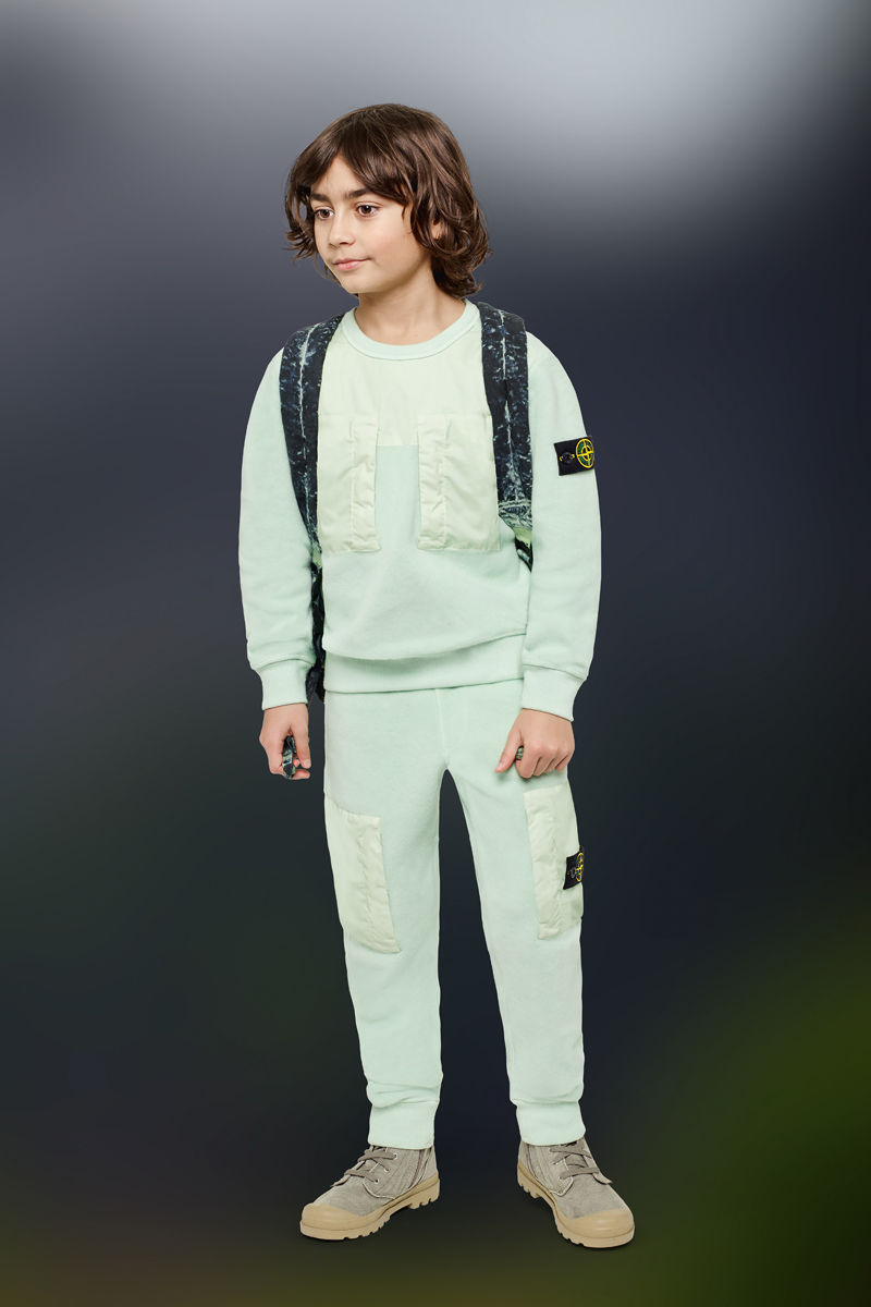 Junior model wearing sand boots, light green cargo pants, a matching crewneck sweatshirt with the Stone Island badge on the upper left arm and a backpack with camouflage shoulder straps.