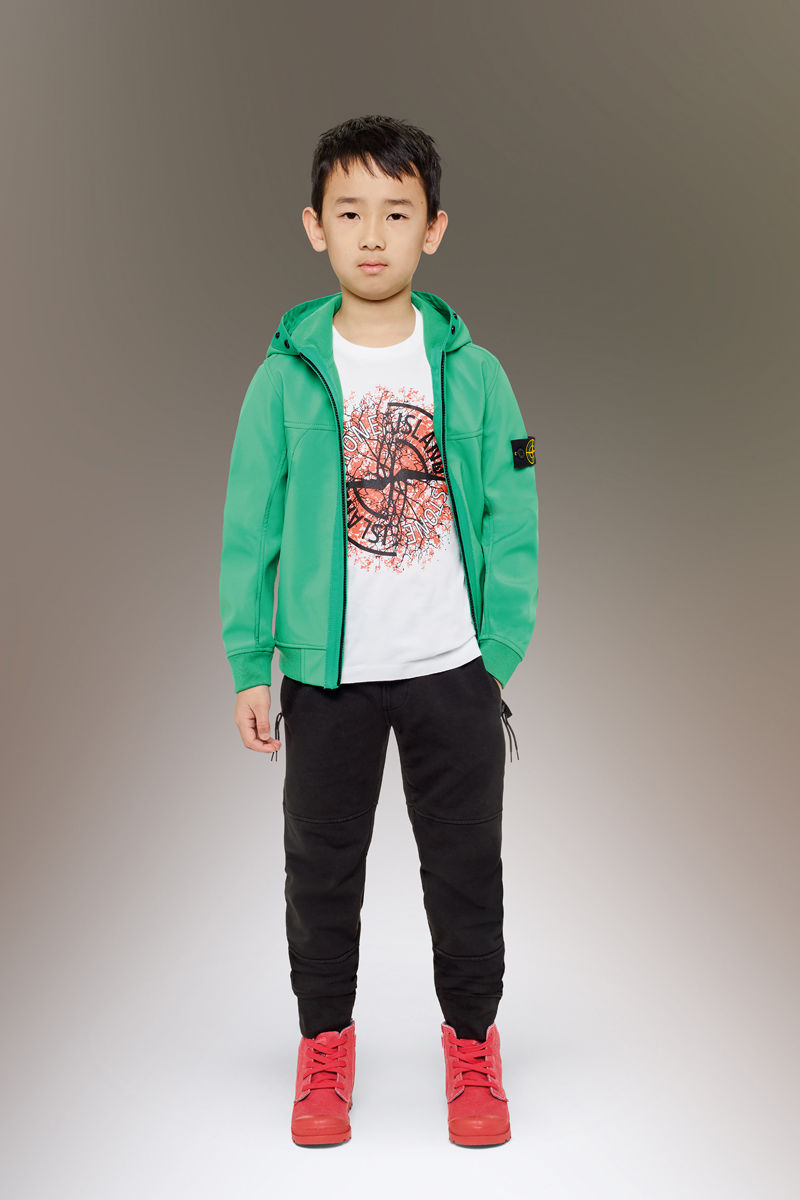 Junior model wearing red sneakers, black pants with slanting hand pockets, a white t shirt with a colorful print and the Stone Island compass logo, and a bright green sweatshirt with hood and zipper fastening.