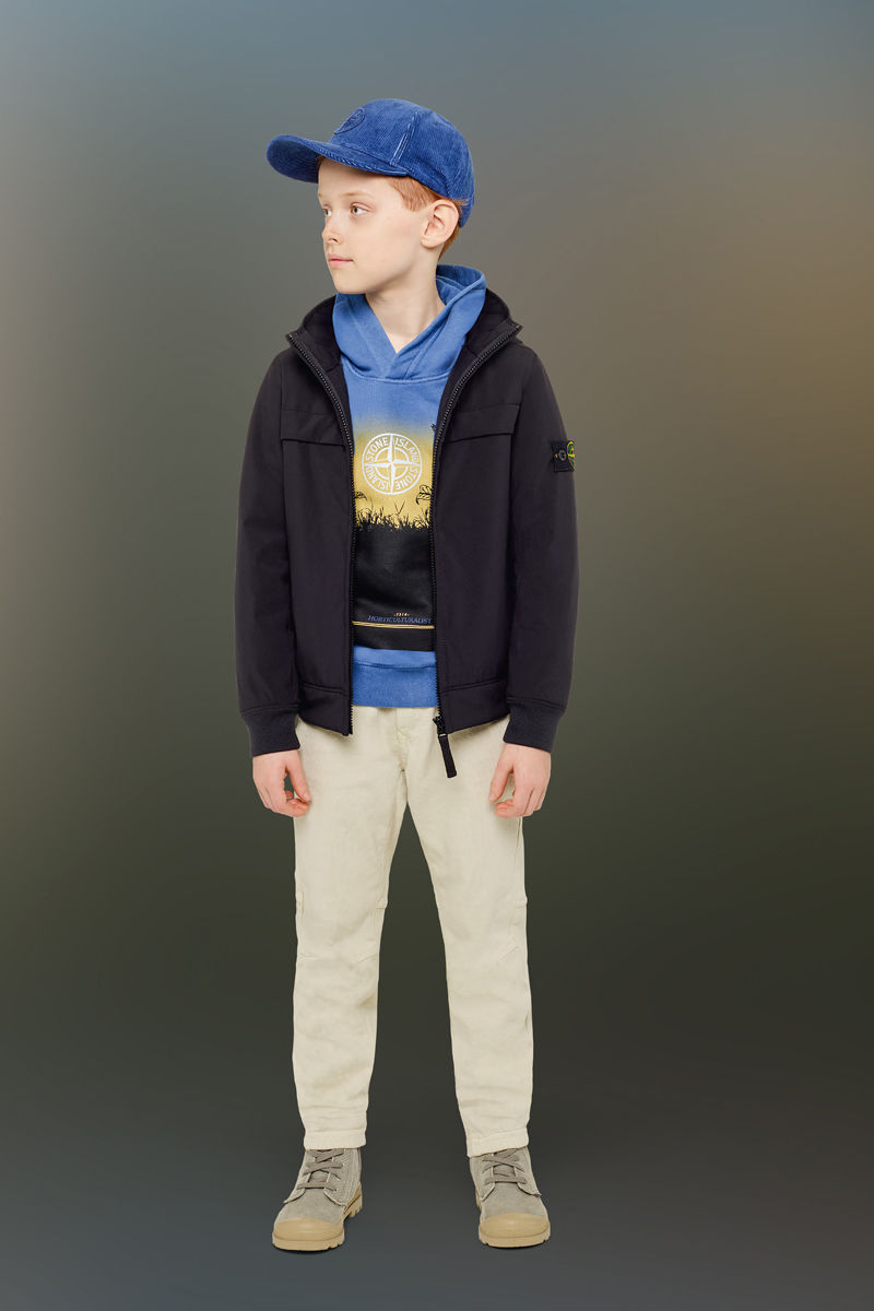 Junior model wearing sand boots, beige pants, a blue sweatshirt with hood and a colorful print and the Stone Island compass logo, a blue cap and a dark colored jacket with standing collar and zipper fastening.