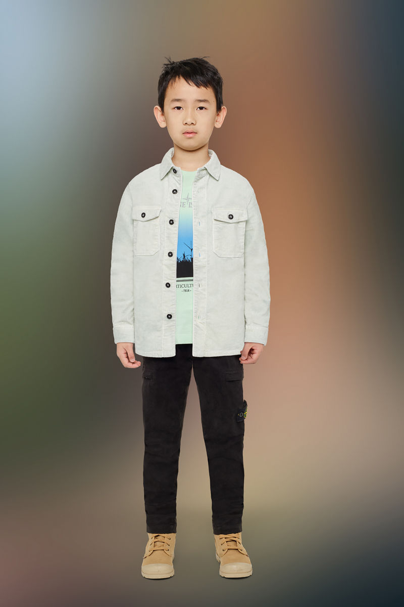 Junior model wearing sand boots, black cargo pants, a light green t shirt with a colorful print on the front and an off white long sleeved shirt with button fastening and two bellows patch pockets on chest with flap and button fastening.