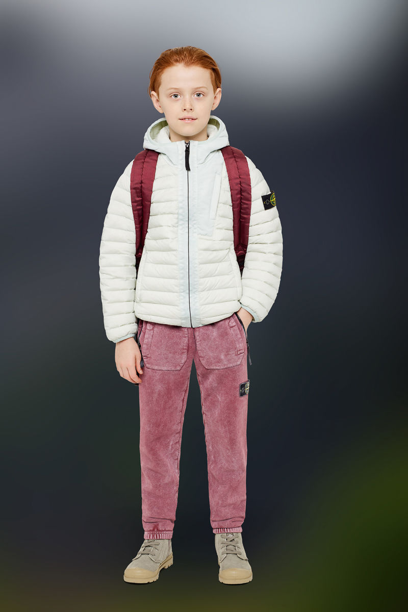 Junior model wearing sand boots, sprayed effect red pants with elasticated cuffs, a backpack with red shoulder straps and a white down jacket with hood, zipper closure and the Stone Island badge on the upper left arm.