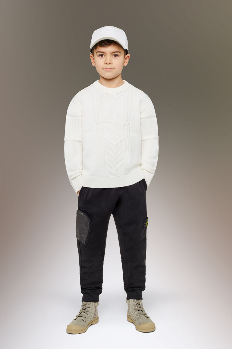 Junior model wearing sand boots, black cargo pants with slanting hand pockets and the Stone Island badge on the left thigh, a white crewneck sweater and a white cap.