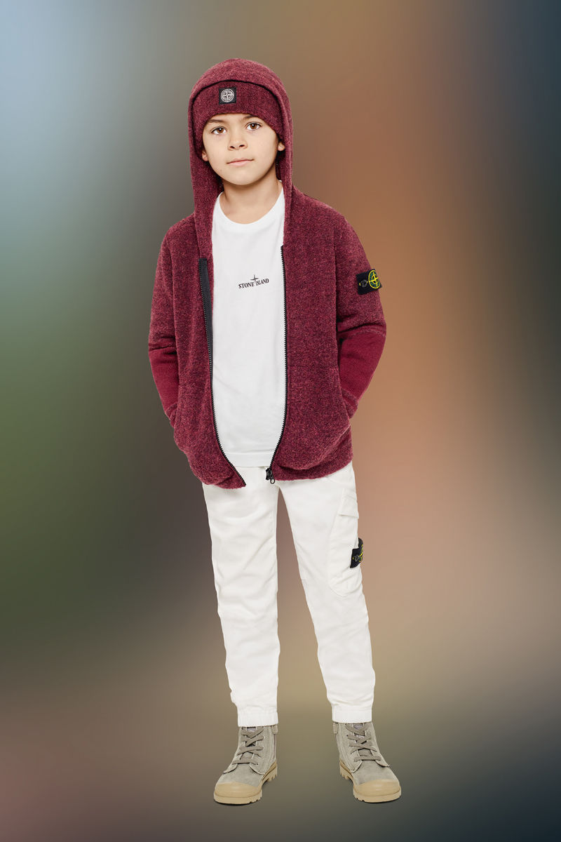 Junior model wearing sand boots, white cargo pants with elasticated cuffs, a white t shirt with tiny Stone Island logo at chest, a burgundy hooded sweatshirt with zipper closure and a matching beanie with the Stone Island Compass Rose patch.
