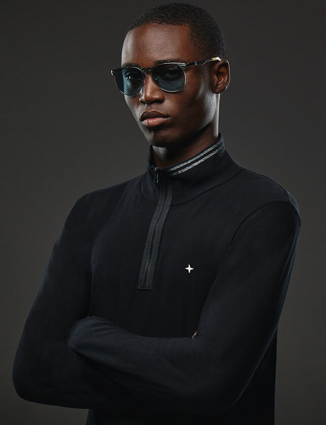 Upper body shot of a model wearing a pair of sunglasses with gray metal frame, blue drop shape lenses, a large metal bridge, adjustable nosepads and a black sweatshirt with high collar, half zipper fastening and the Stone Island star on the chest.