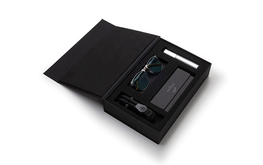 Still life image of an opened black rectangular box showing the items contained inside: a pair of metal frame glasses, a toggle with the Stone Island logo, a metal cylinder and a case with both the Stone Island and the Persol logos on the flap.