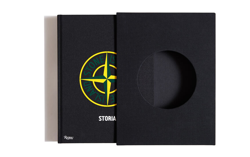 Still life image of a black case with a central round opening and a sliding out hardcover black book with the green and yellow Stone Island compass logo and the title Storia.