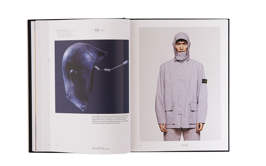 Still life image of an open hardcover book showing printed text and a picture of hood mold on the left page and a model wearing an off white jacket with the same shape hood on the right page.