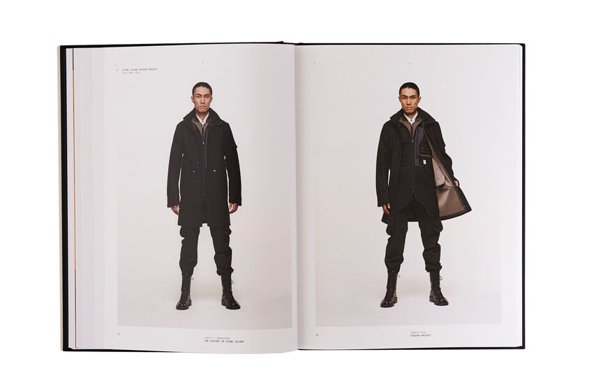 Still life image of an open hardcover book showing a picture of a model wearing black boots, pants and long jacket on the left page and the same model in the same outfit showing the internal lining of the jacket on the right page.