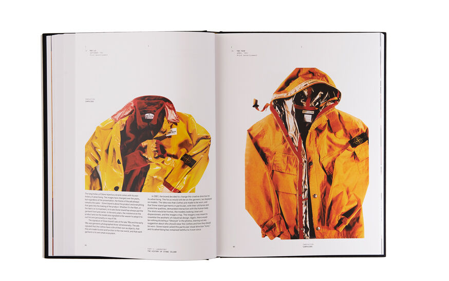 Still life image of an open hardcover book showing printed text and a still life image of a dark yellow jacket with red details on the left page and a still life image of a dark yellow hooded jacket with silver lining on the right page.