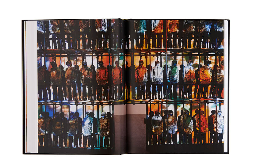 Still life image of an open hardcover book showing across both pages a picture of an installation of many mannequins wearing hooded jackets.