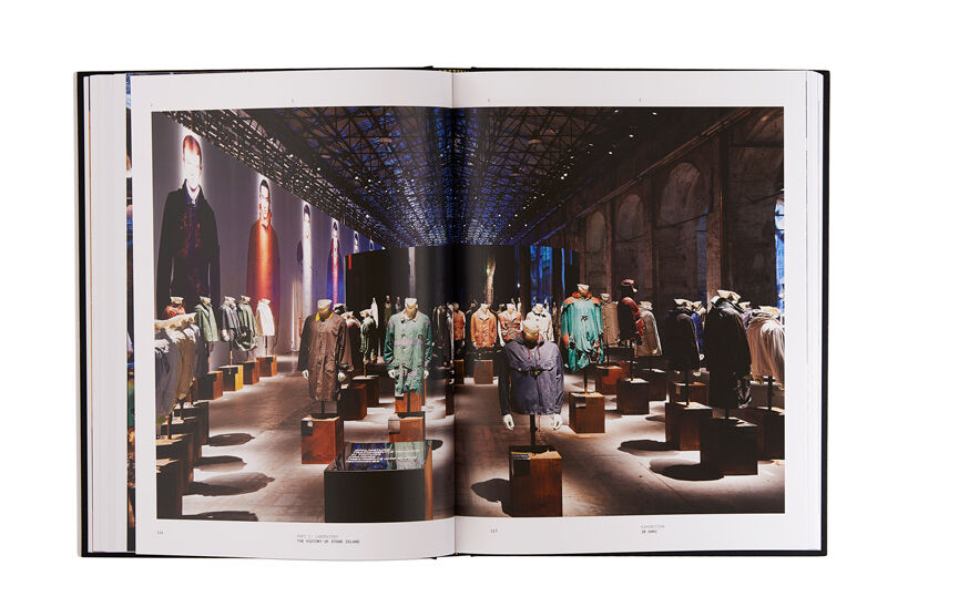 Still life image of an open hardcover book showing across both pages a picture of an installation of many mannequins wearing jackets in different colors and styles.