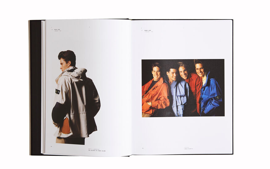 Still life image of an open hardcover book showing pictures of past Stone Island collections, an off white hooded jacket on the left page and four models wearing jackets in different colors on the right page.