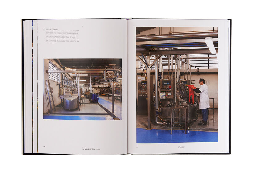 Still life image of an open hardcover book showing printed text and a picture of the interior of a factory on the left page and a man working on a machine in the factory on the right page.