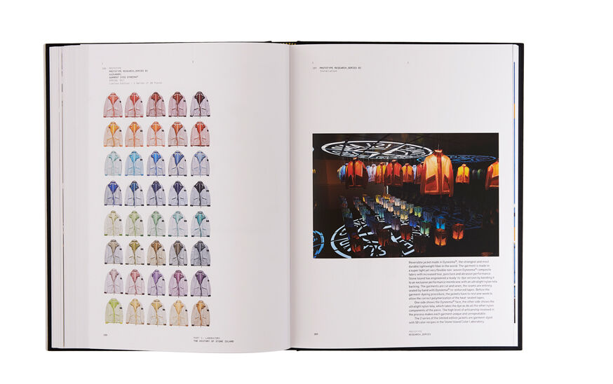 Still life image of an open hardcover book showing printed text and jackets in a variety of colors on the left page and printed text and an installation with jackets of different colors hanging from the ceiling on the right page.
