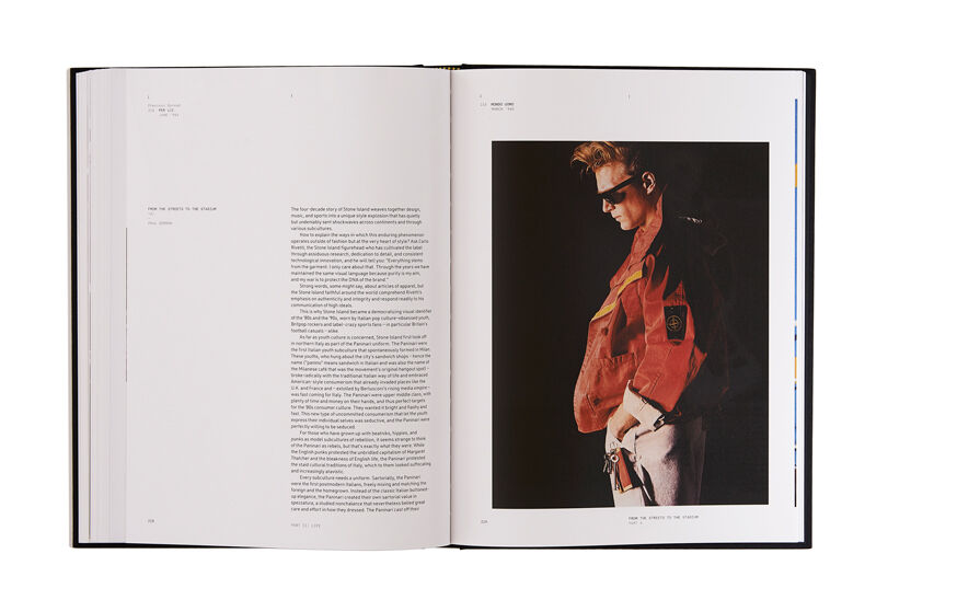 Still life image of an open hardcover book showing printed text on the left page and a model wearing white pants and a red jacket on the right page.