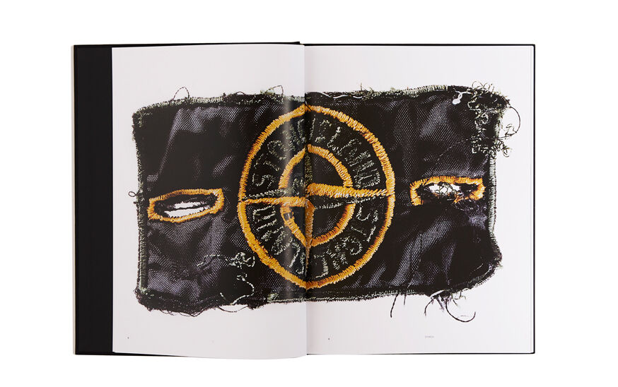 Still life image of an open hardcover book showing a close up shot of the Stone Island badge across both pages.