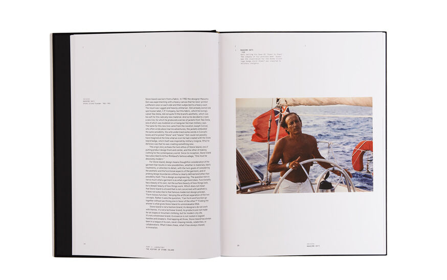 Still life image of an open hardcover book showing printed text on the left page and a picture of Massimo Osti shirtless at the boat\'s wheel on the right page.