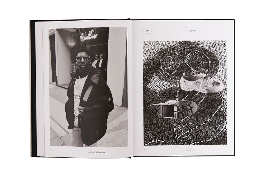 Still life image of an open hardcover book showing two black and white pictures, a man wearing a dark jacket on the left page and a pair of shoes placed on mosaic tiles on the right page.
