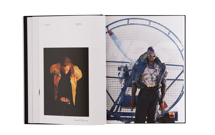 Still life image of an open hardcover book showing a picture of a model in a yellow jacket on the left page and a model wearing pinstriped pants and a khaki jacket on the right page.
