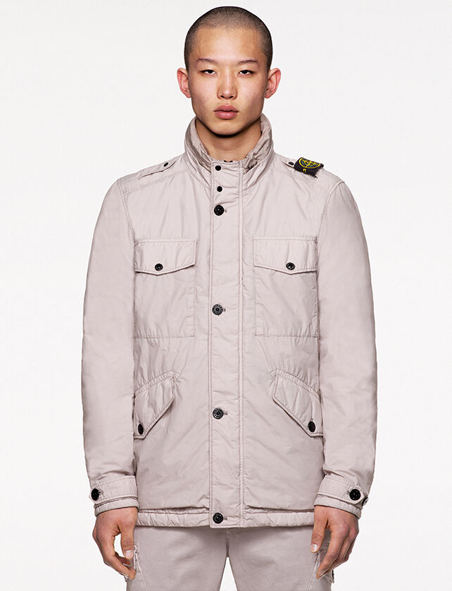 Model wearing off white pants and a matching field jacket with standing collar with two snap fastening, chest and hand pockets with flap and snap fastening and the Stone Island badge on the left shoulder.