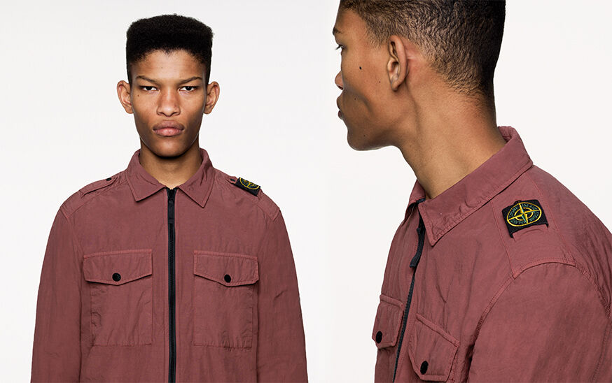 Two close up shots of the same model, from the front and side, wearing a burgundy overshirt with chest patch pockets with flap and snap fastening, zipper closure and epaulettes on the shoulders, the left one carrying the Stone Island Compass badge.