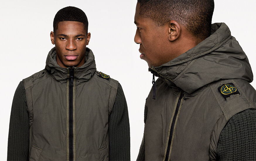 Two close up shots of the same model, from the front and side, wearing a military green hooded jacket with wool knit sleeves, zipper closure and epaulettes on the shoulders, the left one carrying the Stone Island Compass badge.
