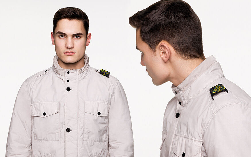 Two close up shots of the same model, from the front and side, wearing an off white field jacket with standing collar, chest patch pockets with flap and snap fastening, zipper closure hidden by a flap with button fastening and epaulettes on the shoulders,