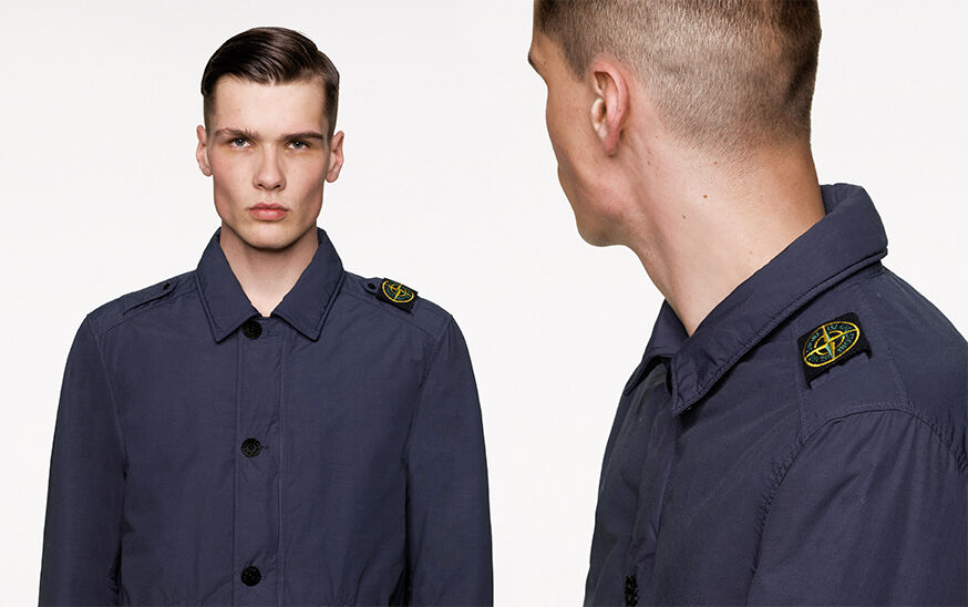 Two close up shots of the same model, from the front and side, wearing a dark blue jacket with shirt collar, button fastening and epaulettes on the shoulders, the left one carrying the Stone Island Compass badge.