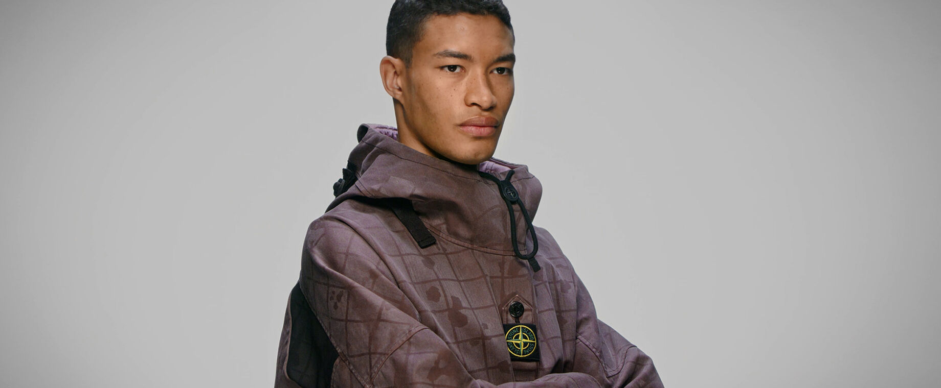 Close up of model wearing burgundy check and paint splatter print anorak with standing collar, toggle and central buttoned strap bearing the Stone Island badge.